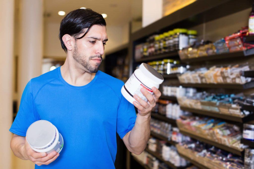 A shopper comparing supplements in a supplement store.
