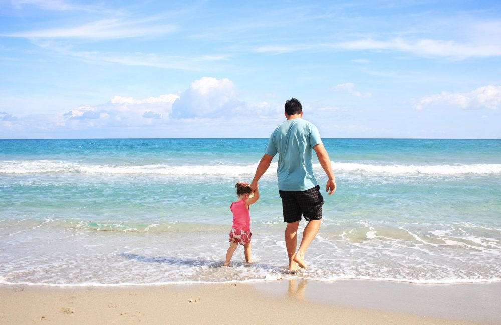 A picture of a father and daughter walking on the beach